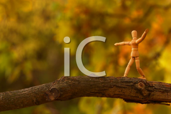 Royalty Free Photo of a Wooden Man on a Branch