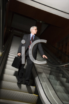 Royalty Free Photo of a Businessman on an Escalator Holding a Briefcase