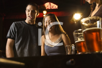 Royalty Free Photo of a Couple Teamed Up at a Foosball Game in a Pub
