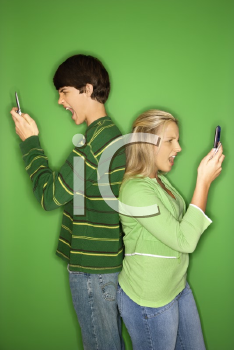 Royalty Free Photo of a Teen Boy and Girl Standing Back to Back Looking at Their Cellphones