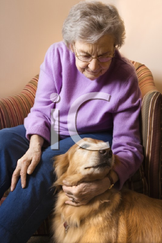 Royalty Free Photo of an Elderly Woman in a Bedroom at Retirement Community Center Petting the Therapy Dog