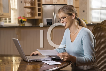 Royalty Free Photo of a Woman Paying Bills on a Laptop Computer