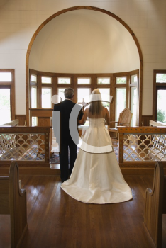 Royalty Free Photo of a Bride and Groom at the Alter of a Church