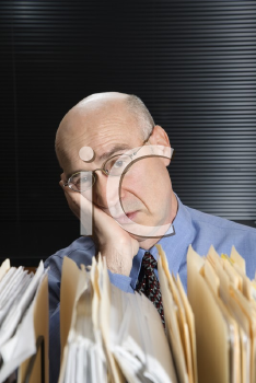 Royalty Free Photo of a Middle-Aged Businessman With Files Leaning Head on Hand Looking Tired