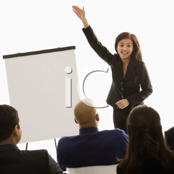 Royalty Free Photo of a Woman Standing in Front of a Business Group Pointing to a Presentation