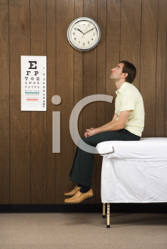 Royalty Free Photo of a Man Waiting on a Table in a Retro Doctor's Office