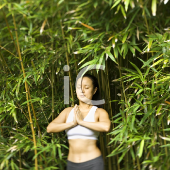 Royalty Free Photo of a Woman in Fitness Attire Standing in a Yoga Position with Eyes Closed in Bamboo Forest in Maui, Hawaii
