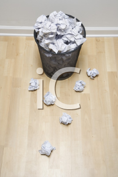 Royalty Free Photo of a Wire Mesh Trash Can With Crumpled Paper Scattered Around