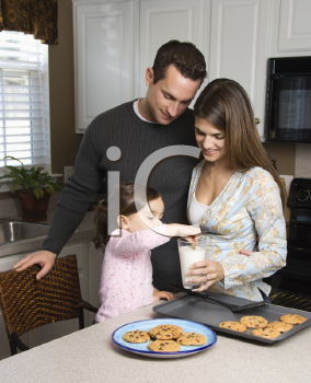 Royalty Free Photo of a Mother and Father Watching Their Daughter Eat Cookies