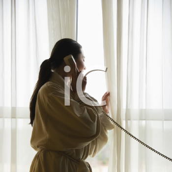 Royalty Free Photo of a Woman in a Bathrobe Talking on the Phone and Looking Out the Window