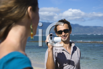 Royalty Free Photo of a Man on a Beach Pointing a Video Camera at a Woman