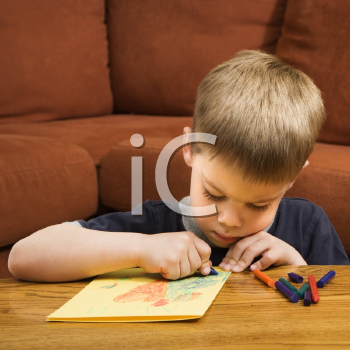 Royalty Free Photo of a Boy Drawing With Crayons