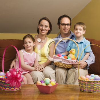 Royalty Free Photo of a Family Sitting on a Couch Holding Easter Baskets and Smiling