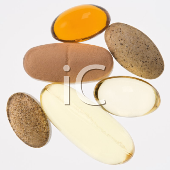 Close up of supplement vitamin pills against white background.