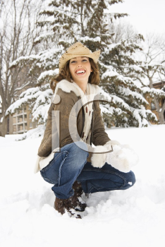 Royalty Free Photo of a Woman Kneeling in the Snow With a Snowball and Wearing a Cowboy Hat