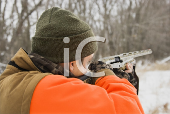 Royalty Free Photo of a Man Aiming a Shotgun Out Towards the Woods