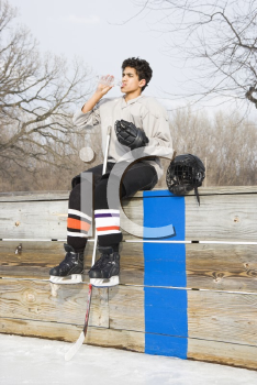 Royalty Free Photo of a Boy in an Ice Hockey Uniform Sitting on the Sidelines Drinking Water
