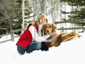Royalty Free Photo of a Woman hugging dog and smiling in snow covered Colorado landscape