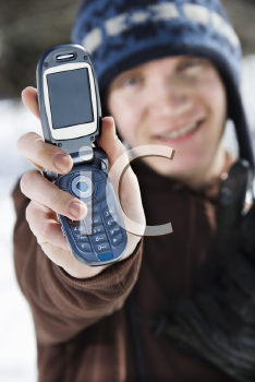 Caucasian male teenager holding out cellphone towards viewer.