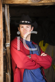 Royalty Free Photo of a Man Wearing a Cowboy Hat With Arms Crossed Leaning Against a Doorway