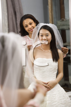 Royalty Free Photo of a Bride and Her Friend Admiring the Dress in the Mirror