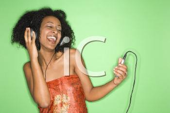 Royalty Free Photo of an African American Woman Listening to Music Through Headphones