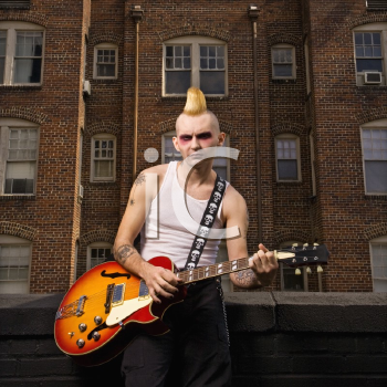 Royalty Free Photo of a Male Punk Playing Guitar With a Building in the Background
