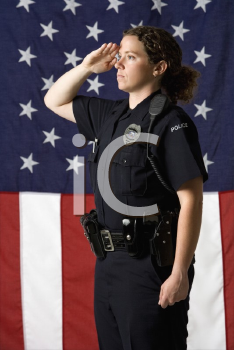 Royalty Free Photo of a Policewoman Saluting With an American Flag as a Backdrop
