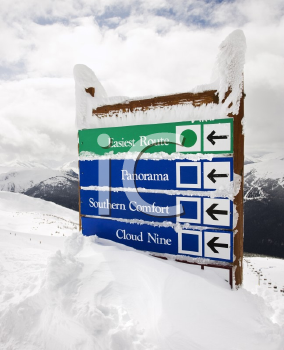 Royalty Free Photo of Snow Covered Sign With Arrows to Slopes