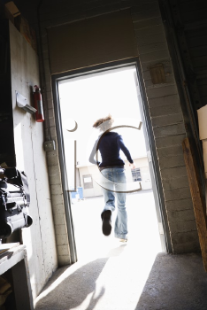 Royalty Free Photo of a Woman Running Through an Open Door From a Building to Sunny Outside