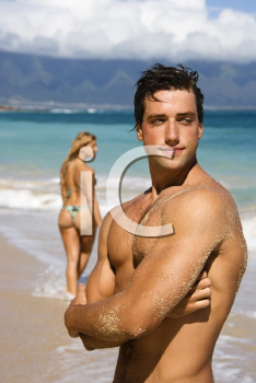 Royalty Free Photo of a Handsome Man Standing on Maui, Hawaii Beach With a Woman in the Background
