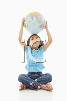 Asian girl sitting on floor holding Earth globe over her head.