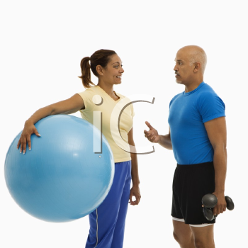 Royalty Free Photo of a Man Standing Next to a Woman Holding an Exercise Ball