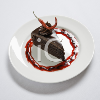 Slice of chocolate cake on dessert plate adorned with a red chili pepper.