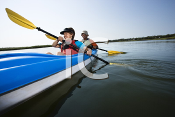 Royalty Free Photo of a Low Angle of African American Middle-aged Man and Woman Paddling Kayak
