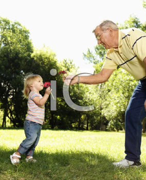 Royalty Free Photo of a Grandfather and Granddaughter Holding Flowers and Smelling