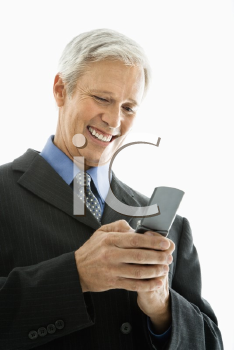 Royalty Free Photo of a Businessman Smiling and Text Messaging on a Cellphone