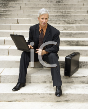 Royalty Free Photo of a Middle-Aged Businessman Sitting on Steps Outdoors With a Laptop and Briefcase