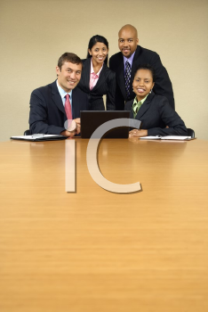 Royalty Free Photo of Businesspeople Gathered Around a Laptop Computer Smiling