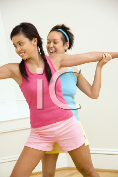 Royalty Free Photo of a Woman Helping Another Woman With Positioning on Her Yoga Pose