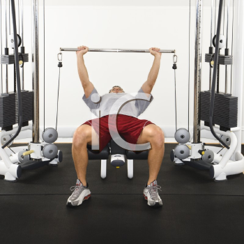 Royalty Free Photo of a Man at a Gym Lifting Weights on a Weight Machine