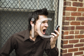 Royalty Free Photo of an Angry Man Yelling Into a Cellphone