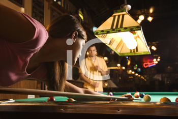 Young woman playing billiards with a young man in the background.  Horizontal shot.