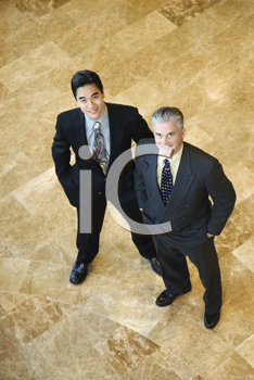 Two business men stand on a marble floor with hands in their pockets. They are looking up towards the camera. Vertical shot.