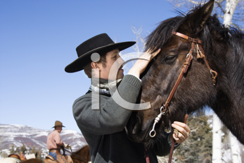 Attractive young man wearing a cowboy hat. He is petting a horse with another rider in the background. Horizontal shot.