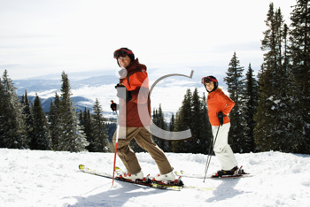 Side view of skiers on a snowy ski slope with trees and valley in background. Horizontal shot.