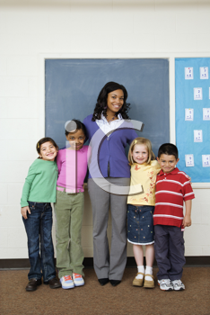 Teacher posing for group portrait with students in school classroom. Vertically framed shot.