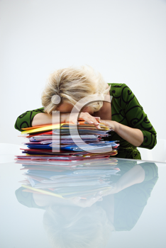 Caucasian middle aged businesswoman sitting at office desk with head down on top of pile of folders.