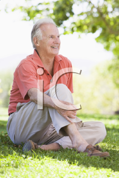 Royalty Free Photo of a Man Sitting on the Lawn