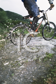 Royalty Free Photo of a Guy Jumping Water on a Bike